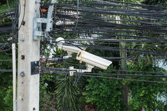 Security camera on electric pole with maze electric cables Stock Image