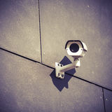 Security camera on gray office building wall Stock Photography