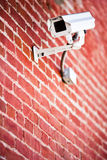 Security camera mounted on brick wall Stock Photo