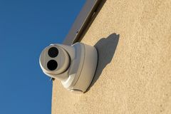 Security camera mounted on a wall, pointed straight at the viewer, closeup stock photography