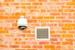 Security camera on orange brick wall Stock Images