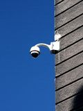 Security camera on plaster covered wall against deep blue sky Royalty Free Stock Photography