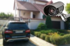 Camera and private house on the background. Security camera and private house on the background alarm cctv electronic equipment lens protect record safety stock image
