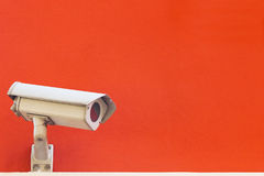 Security camera on a red wall background. Stock Photos