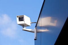 Security camera reflected on shiny building facade Royalty Free Stock Photo