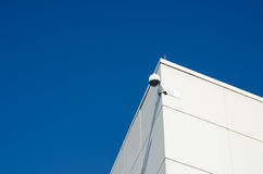 A security camera set against a brilliant blue sky. A security camera keeps tabs on the exterior of a white office building stock photography