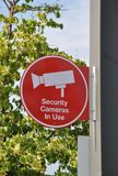 Security camera in use sign. Posted in a metal post vector illustration