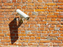 Security camera on the wall. Modern security camera on an old brick wall Stock Photography