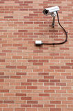 Security Camera Watching. A security camera pointed to the left with a red brick background royalty free stock images