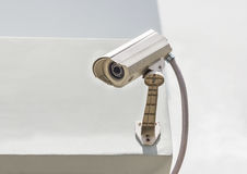 Security camera on the white wall. Stock Photo