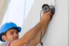 Security Camera. Young man setting security camera system Stock Image