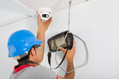 Security Camera. Young man setting security camera system stock images