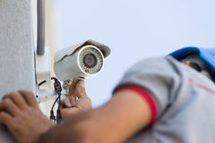 Security Camera. Young man setting security camera system royalty free stock image