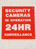 Security cameras in 24 hour operation. An image of a red security warning sign on a brick wall to show the danger that we are all being watched round the clock Stock Photos