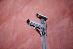 Security cameras. A pair of security cameras on a red wall Stock Image