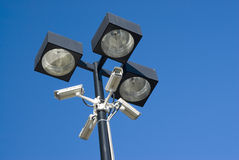 Security cameras. Mounted on floodlights in a parking lot Stock Images
