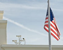 Security Cameras and American Flag. Security cameras on tope of a building with an American Flag next to them Royalty Free Stock Images