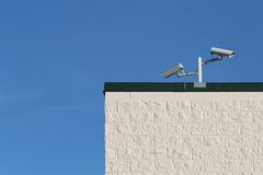 Security cameras on building. Security cameras on a building monitoring the surrounding activities Stock Photography