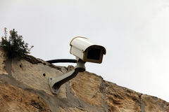 Security cameras fitted to a roof against a  winter sky. Royalty Free Stock Photo