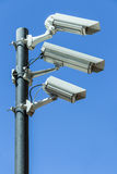 Security cameras on pole. Three surveillance cameras attached to a pole on a blue sky background with copy space Royalty Free Stock Images
