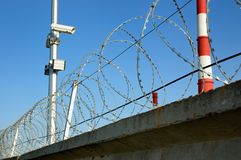 Security cameras. And razor wire against a blue sky royalty free stock photography