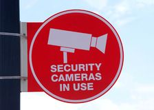 Security cameras in use sign with sky in background Stock Photos
