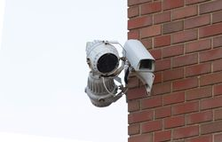 Security cameras watch a building. Security cameras on guard over a building stock image