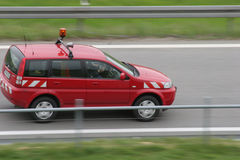 Security car. Red security car driving down a road Stock Image