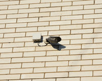 Security CCTV camera is mounted on a white brick house wall outdoor. Stock Photos