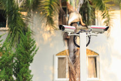 Security CCTV camera operating in front of building Royalty Free Stock Image