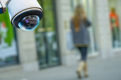Security CCTV camera or surveillance system with a pedestrian on blurry background. Closeup on security CCTV camera or surveillance system with a pedestrian on stock images