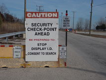 A security check point sign. A caution security check point sign at the entrance of a  factory. Road, sky and foliage in back round Stock Images