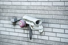 Security closed circuit television CCTV camera. Covered in mold and moss on the bricked wall royalty free stock photos