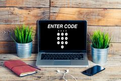 ENTER CODE in a laptop screen placed on a wooden desk Stock Image