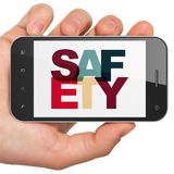 Security concept: Hand Holding Smartphone with Safety on display. Security concept: Hand Holding Smartphone with Painted multicolor text Safety on display, 3D stock images