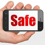 Security concept: Hand Holding Smartphone with Safe on display. Security concept: Hand Holding Smartphone with red text Safe on display, 3D rendering Royalty Free Stock Photography