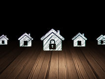 Security concept:  home icon in grunge dark room. Security concept: row of Glowing home icons around home icon in grunge dark room Wooden Floor, dark background Royalty Free Stock Photo