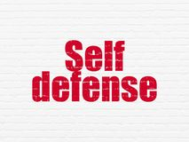 Security concept: Self Defense on wall background. Security concept: Painted red text Self Defense on White Brick wall background Stock Images