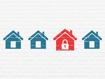 Security concept: red home icon on wall background Stock Photo