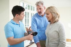 Security Consultant Demonstrating Alarm System To Mature Couple Stock Image