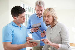 Security Consultant Demonstrating Alarm System To Mature Couple Royalty Free Stock Photos