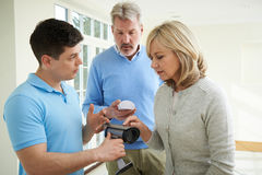 Security Consultant Demonstrating Alarm System To Mature Couple Royalty Free Stock Photography