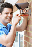 Security Consultant Fitting Camera To House Wall. Security Consultant Fits Camera To House Wall Royalty Free Stock Image
