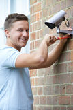 Security Consultant Fitting Security Camera To House Wall Royalty Free Stock Image