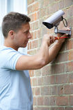Security Consultant Fitting Security Camera To House Wall. Security Consultant Fits Security Camera To House Wall Stock Photography