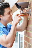 Security Consultant Fitting Security Camera To House Wall. Security Consultant Fits Security Camera To House Wall Stock Photos