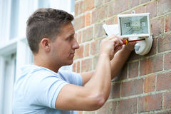 Security Consultant Fitting Security Light To House Wall. Security Consultant Fitting Security Light To House Stock Images