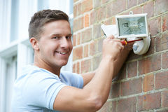 Security Consultant Fitting Security Light To House Wall Royalty Free Stock Photography