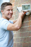 Security Consultant Fitting Security Light To House Wall. Security Consultant Fits Security Light To House Wall Stock Photography