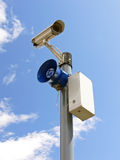 Security equipment. Closeup of the post with loud-speaker and security surveillance camera with the beauty blue sky in the background stock photography